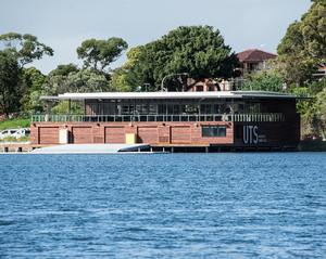 The rowing club building sitting on the waterfront with a large balcony and boat jetty