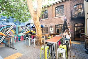 Outside the Loft, a leafy courtyard with stools, tables and a wall mural