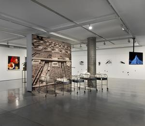 An exhibition in the industrial gallery space with paintings and sculptures